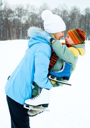 happy young mother going ice skating with her little son