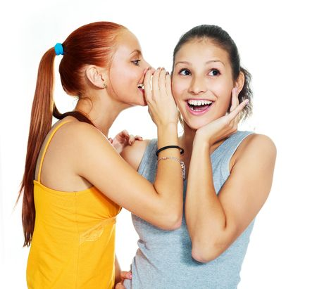 Photo pour portrait of two beautiful gossiping girls against white background - image libre de droit
