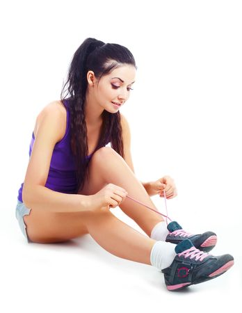 pretty brunette girl wearing sports clothes tying shoelaces