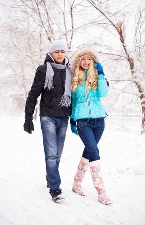 happy young beautiful couple having a walk in winter park (focus on the woman)