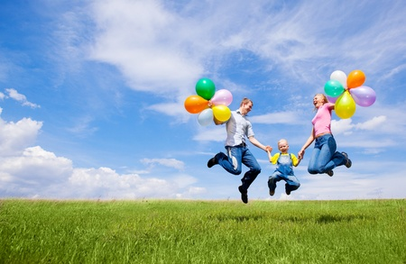 Foto de happy jumping family with balloons outdoor on a summer day - Imagen libre de derechos