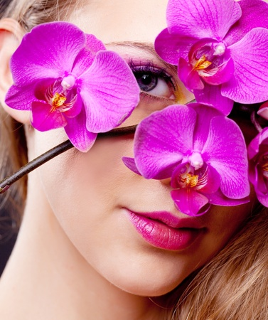 portrait of a beautiful young blond woman with an orchidの写真素材