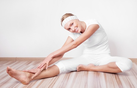 beautiful young blond woman stretching the muscles of her back and legs  at home