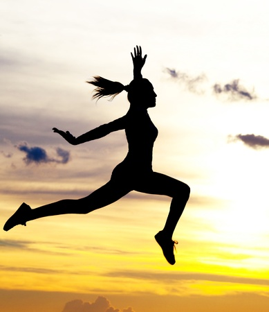 Photo for Silhouette of a beautiful jumping woman against yellow sky with clouds at sunset - Royalty Free Image