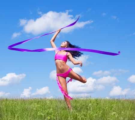 happy dancing young woman with a ribbon outdoor on a summer day