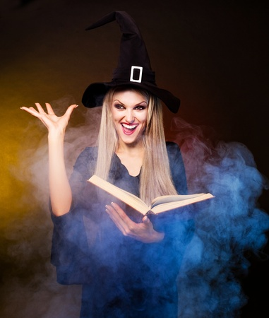 angry  blond witch with a book and her hands and clouds of blue smoke around her conjuring, against black and yellow background
