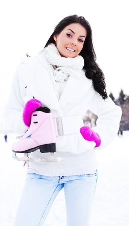 happy beautiful girl wearing warm winter clothes going to ice skate