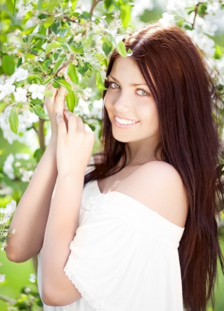 beautiful young brunette woman with the apple tree on a warm summer day