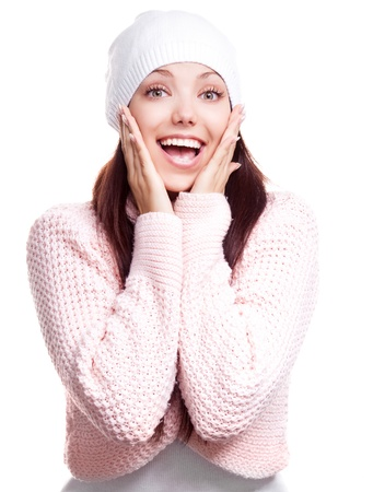 beautiful happy surprised young woman wearing a high neck sweater and a hat, isolated against white backgroundの写真素材