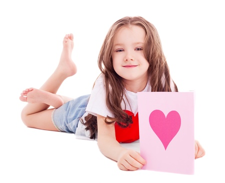cute six year old girl  with a Valentine's card in her hands, isolated against white background