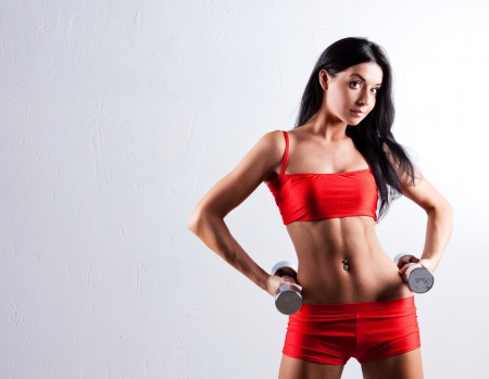 Foto de high contrast studio portrait of a beautiful sporty muscular woman working out with two dumbbells, copyspace to the left - Imagen libre de derechos