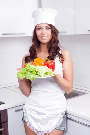 beautiful young woman with vegetables in the kitchen at home