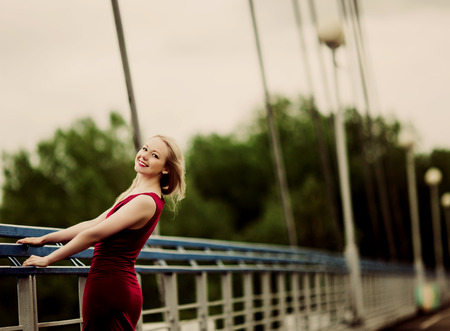 beautiful happy blond woman on the bridge on a summer day
