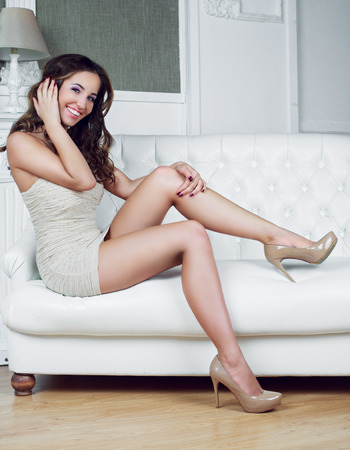 Foto de beautiful young model with an amazing slim body and curly hair wearing a dress, in the interior - Imagen libre de derechos