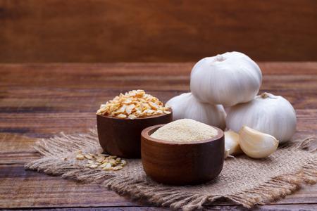 Foto für garlic cloves, bulb, flakes and powder on old wooden board - Lizenzfreies Bild