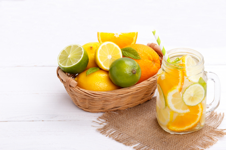 Citrus lemonade infused water with lemon lime and orange. Healthy detox drink on white wooden table