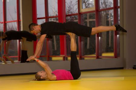 Photo pour Couple practicing bird pose during yoga class in modern fitness center. Acro yoga - image libre de droit
