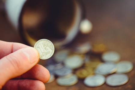 the fall of the Russian ruble, the coin in hand poverty and poverty scattered coins in the old circle on a rusty background, sanctions and the collapse of the economy.