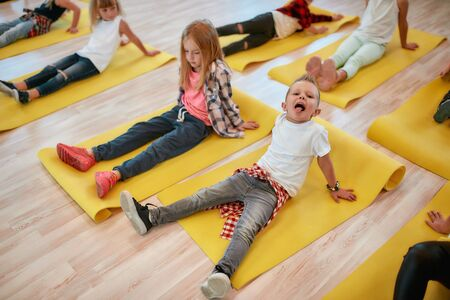 Photo pour Making funny face. Close up portrait of cute boy sitting on the yellow yoga mat and sticking out his tongue while having a yoga class in the dance studio - image libre de droit
