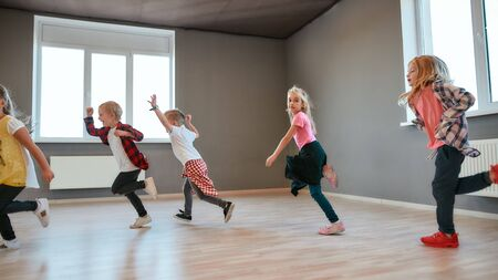 Full of energy. Little and happy boys and girls running in the dance studio. Warming up before dance class