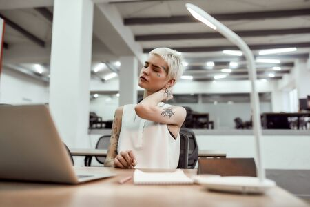Photo pour Exhaustion. Young attractive tattooed business woman feeling tired and massaging her neck while sitting at her working place in the modern office - image libre de droit
