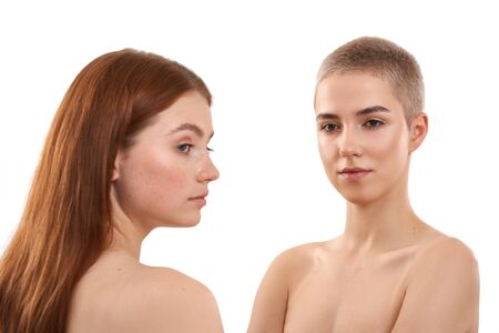 Photo pour Two attractive models with healthy skin posing naked against white background. Young red-haired girl with freckles and blonde with short haircut. Natural beauty - image libre de droit
