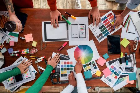 Foto de Mobile app design. Top view of designers discussing sketches, choosing colors from palettes lying on the desk while having a meeting in the modern office - Imagen libre de derechos