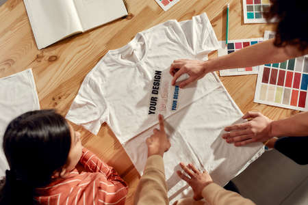 Photo pour Writing that sells. Creative people trying on stickers with text, while discussing logo and design of T-shirt. Young man and women working together at custom T-shirt, clothing printing company - image libre de droit