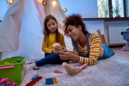 Photo pour A good time for child. African american woman baby sitter entertaining caucasian cute little girl. They are playing with dolls together sitting in wigwam, tent - image libre de droit