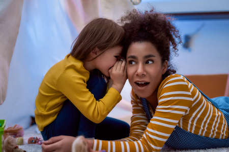 Photo pour Listening is a key. African american woman baby sitter entertaining caucasian cute little girl. They are gossiping and telling secrets sitting in kids room. Leisure activities, babysitting concept - image libre de droit