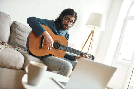 Photo pour Watching video tutorial. Young man sitting on sofa at home and learning guitar online. Sitting on sofa at home and looking at laptop - image libre de droit