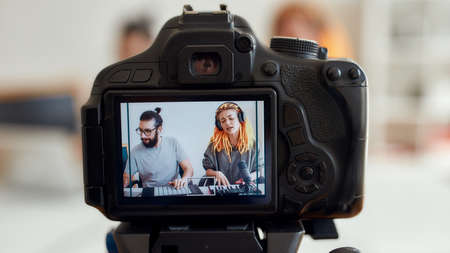 Photo for Woman with dreadlocks singing and playing. Female and male blogger recording making music using synthesizer, drum pad machine. Focus on camera screen - Royalty Free Image