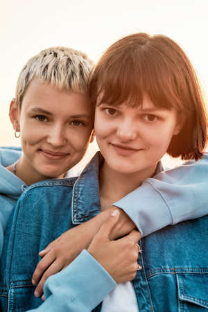 Photo for Portrait of two attractive young women with short hair smiling at camera, Young lesbian couple spending time together, hugging while posing outdoors - Royalty Free Image