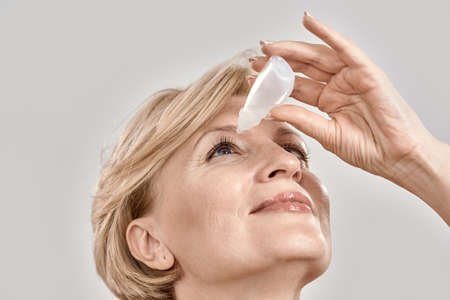 Photo for Close up portrait of attractive middle aged woman applying eye drops, standing isolated over grey background - Royalty Free Image