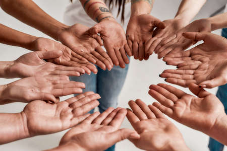 Photo pour Diverse women holding their hands open palm together, making a circle over grey background. Concept of support, racial unity and relations in society - image libre de droit