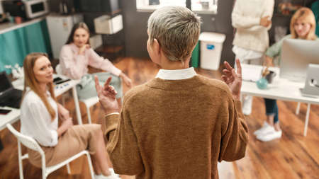 Photo pour A backview of a mature woman wearing fashionable clothes with a short haircut talking to her collaborateurs during a brainstorm - image libre de droit