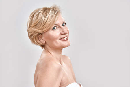 Photo for Portrait of beautiful middle aged woman in white bra smiling at camera, posing isolated against grey background. Beauty concept - Royalty Free Image