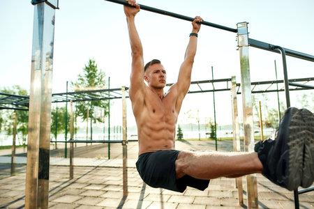 Photo pour Young caucasian sportsman with muscular torso performing corner exercise - image libre de droit
