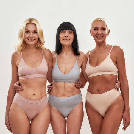 Photo pour Three attractive middle aged women in underwear embracing each other while posing together on light background - image libre de droit
