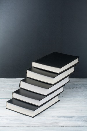 Open books on wooden table, black board background. Back to school. Education business concept.