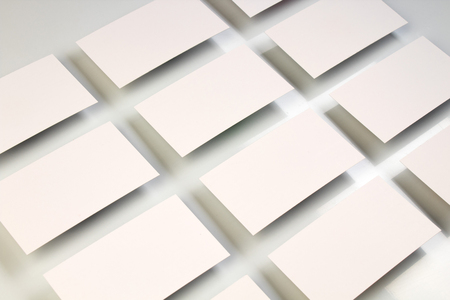 Photo pour Mockup of horizontal business cards stacks arranged in rows at white textured paper background. - image libre de droit
