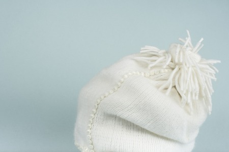 Photo pour image of white cozy knitted cap with wooden table - image libre de droit