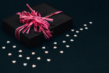 Photo for Vintage black gift box with pink ribbon bow on black background sprinkled with heart shaped confetti. Copy space. - Royalty Free Image