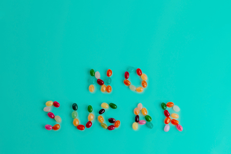 Top view of text made of colorful bean sweet candies on bright turquoise blue background. Healthy food and diet concept. Copy space.