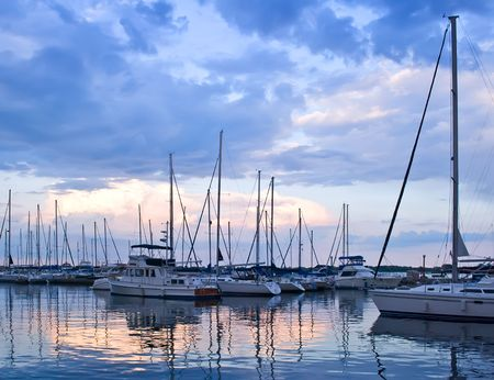 Yachts and boats moored in harbor at sunset
