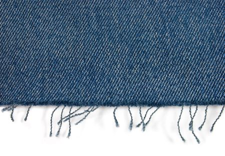 Edge of blue jeans fabric with fringe on white