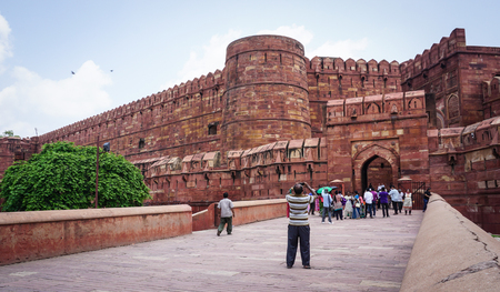 Agra, India - Jul 13, 2015. People visit Agra Fort at the sunny day. The fort was built by the Mughals, can be more accurately described as a walled city in Agra, India.
