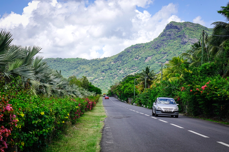 Le Morne, Mauritius - Jan 5, 2017. Cars running on rural road in Le Morne, Mauritius. Mauritius was uninhabited until 1598, and had much unique wildlife and plant life.