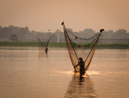 Fishermen working on lake at sunrise in Mandalay, Myanmar. Mandalay is the second-largest city and the last royal capital of Myanmar.