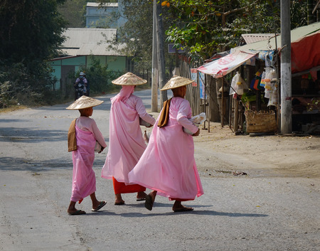Mandalay, Myanmar - Feb 21, 2016. Buddhist nuns walking for morning alms at countryside in Mandalay, Myanmar.